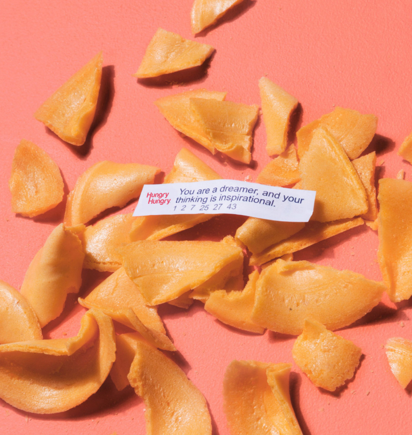 Crushed fortune cookie with HungryHungry branded fortune reading in the centre on pink background