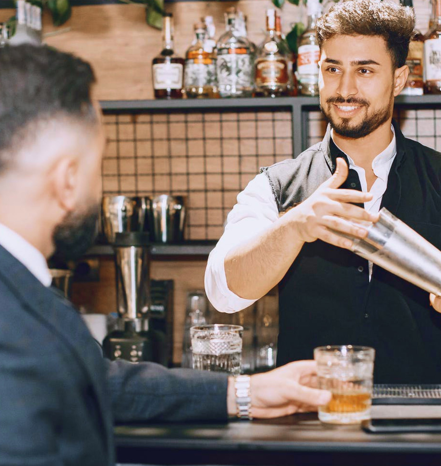 Bartender shaking cocktail with customer blurred in foreground wearing a suit holding cocktail on bar