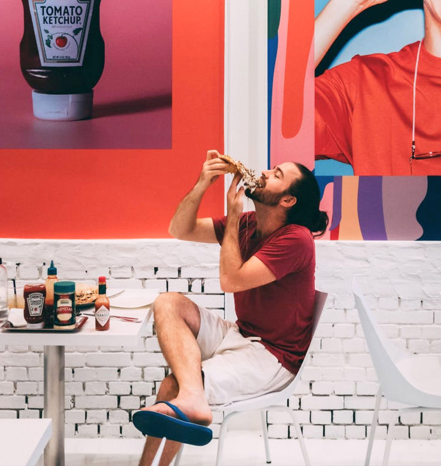 Man eating pizza in flipflops with cheese dripping and condiments on table with big image of ketchup in background