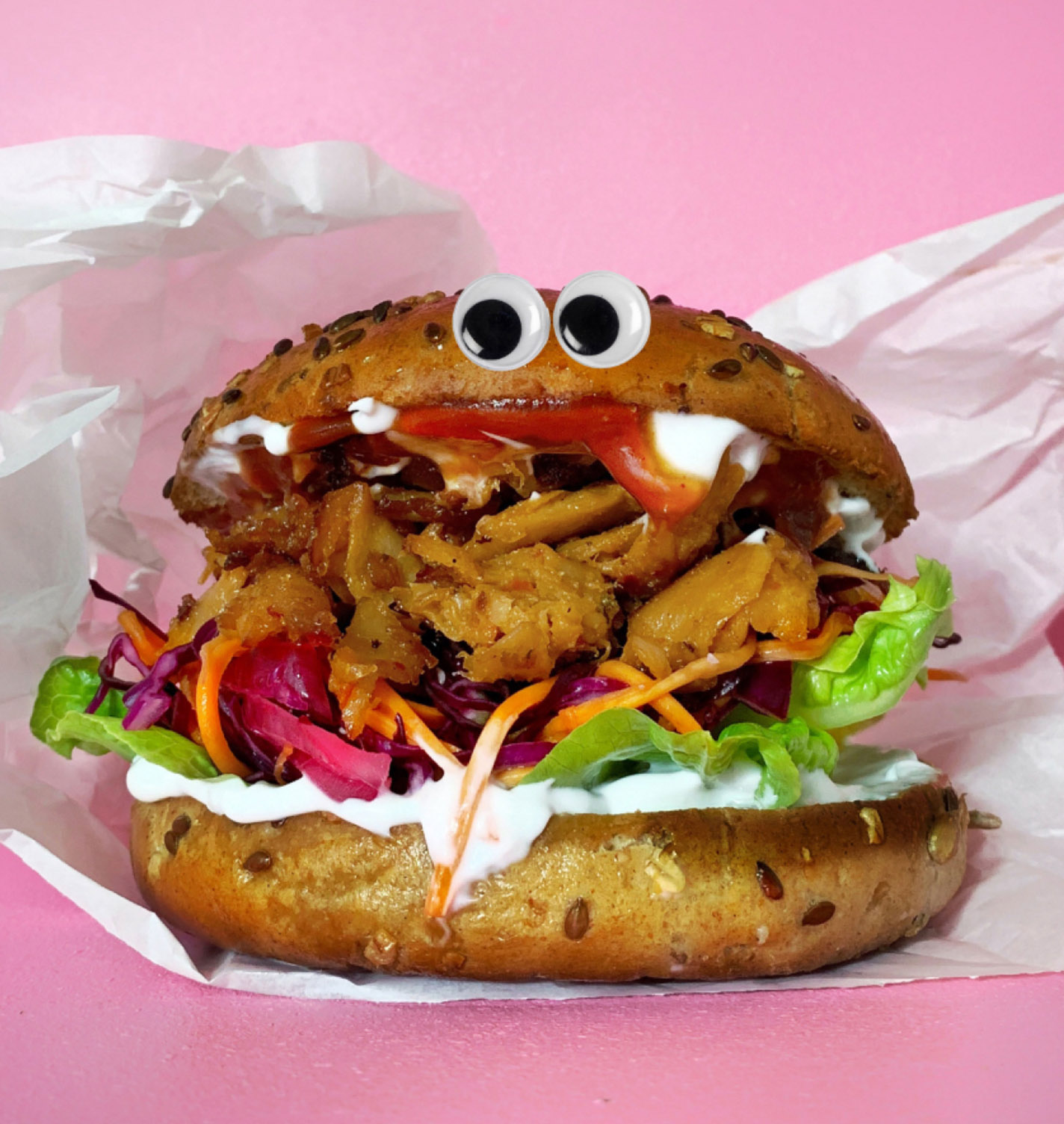 Burger with googly eyes and mayonnaise in paper wrapping on pink background