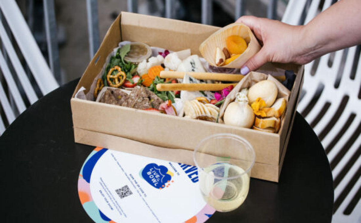 Person holding food from grazing box with Live at the Bowl x HungryHungry QR Code Sticker