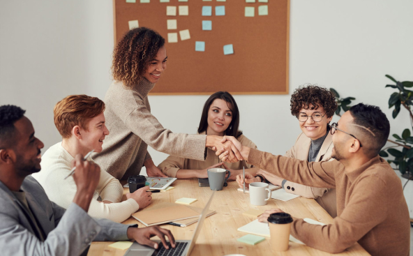 Various coworkers sitting around table in meeting room with two people shaking hands and smiling