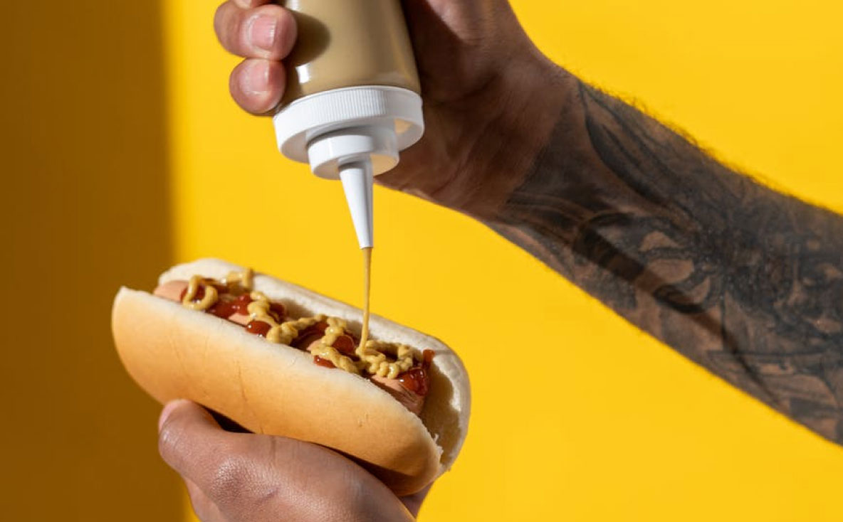 Tattooed arm squeezing mustard on a hotdog on yellow background