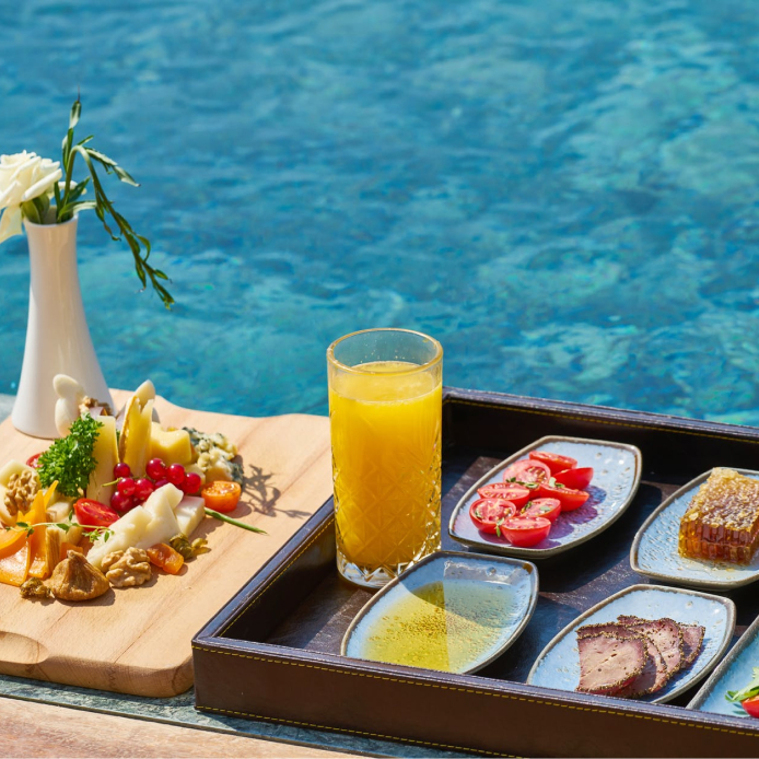 Breakfast platter with various ingredients such as fruit and tomatoes with a glass of orange juice by the pool