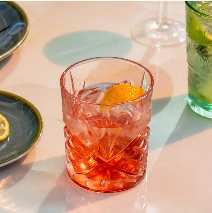 Centred Negroni in a crystal glass surrounded by other various cocktails