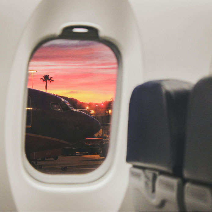 View through airplane window looking onto more planes in a pink sunset